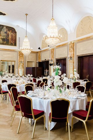 wedding-reception-burgundy-and-gold-velvet-chairs-greenery-white-flower-centerpieces-chandeliers