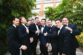 groom-in-navy-blue-suit-and-bow-tie-with-groomsmen-in-black-suits-with-navy-blue-bow-ties