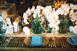 wedding-reception-wood-table-woven-jute-leather-table-runner-candles-white-orchids-blue-vases