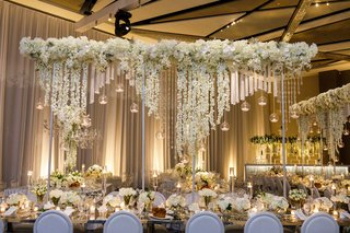 wedding-reception-long-mirror-table-with-tall-riser-overhead-centerpiece-candle-orb-orchids-flowers