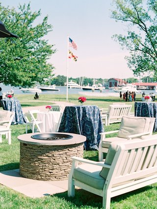 seating-area-and-fire-pit-on-lawn-at-venue-river-view-blue-navy-linens-pink-flowers-lounge-furniture