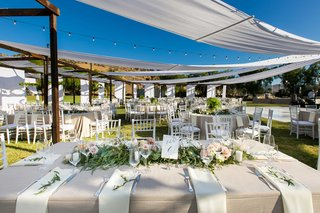 semi-tented-outdoor-reception-space-with-champagne-colored-tablescapes-hanging-lights-low-florals
