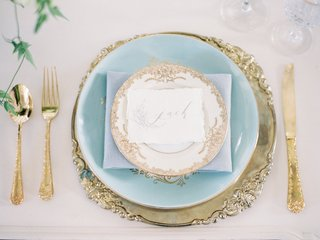 wedding-reception-place-setting-with-a-gold-charger-with-ornate-rim-light-blue-dinner-plate