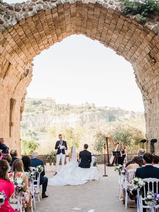 old-abbey-wedding-venue-in-italy-view-of-countryside-umbria-guests-in-white-chairs-terrace-ruins
