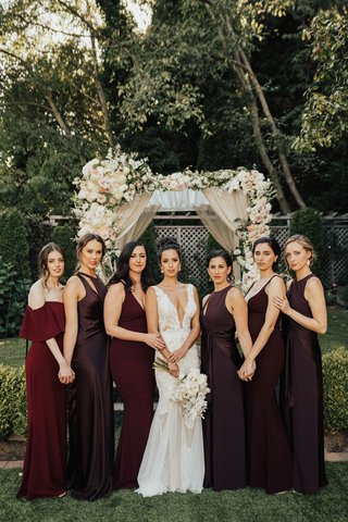 bride-in-low-plunging-neckline-gown-hair-up-with-bridesmaids-in-mismatch-burgundy-oxblood-dresses