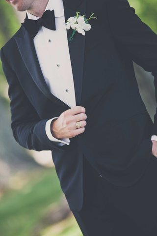 a-close-up-shot-of-a-grooms-black-tuxedo-and-his-white-and-green-boutonneire