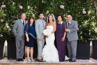 bride-in-a-vera-wang-dress-with-ruffled-skirt-groom-in-grey-suit-and-purple-tie-and-parents