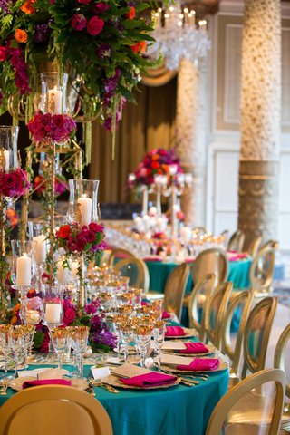vibrant-turquoise-pink-gold-purple-green-reception-tablescape-bright-linen-tall-floral-centerpiece