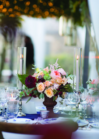 wedding-reception-with-small-floral-arrangement-with-pink-burgundy-peach-flowers-between-candles