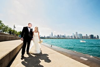bride-in-vera-wang-groom-in-vera-wang-newlyweds-walk-alongside-lake-michigan