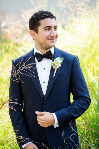 groom-in-navy-blue-tuxedo-jacket-with-black-lapels-buttons-and-bow-tie-natural-boutonniere