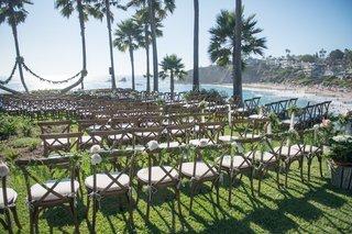 seaside-wedding-ceremony-in-laguna-beach-residence-rustic-chairs-white-flowers-greenery