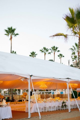beach-tented-reception-with-amber-lighting-crystal-chandeliers-white-linens-flowers-chairs