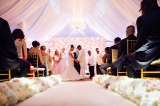 wedding-ceremony-with-white-aisle-runner-cream-and-pink-flowers-white-drapery-flower-wall-altar