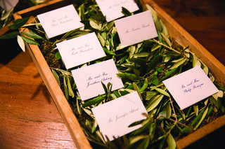 shallow-wooden-box-filled-with-olive-leaves-with-escort-cards-on-top
