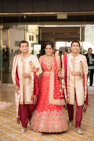 bride-in-red-and-gold-lehnga-gold-jewelry-brothers-of-bride-walking-her-down-aisle
