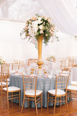 wedding-reception-blue-linen-round-table-gold-chairs-tall-centerpiece-white-orchid-peach-flowers