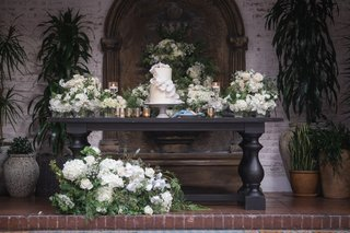 large-table-with-small-wedding-cake-dessert-table-white-flowers-and-greenery