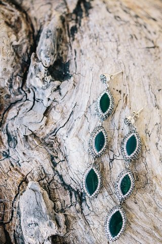 emerald-stones-with-halo-setting-on-tree-bark