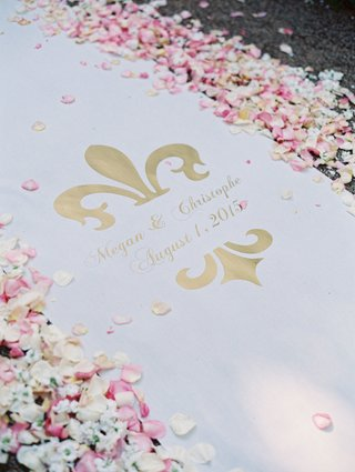 custom-white-aisle-runner-with-bride-and-grooms-names-wedding-date-in-gold-lined-white-pink-petals