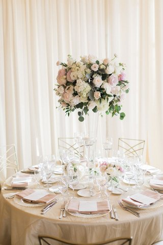 wedding-reception-drapery-tall-centerpiece-white-pink-flowers-greenery-gold-chairs-pink-napkin