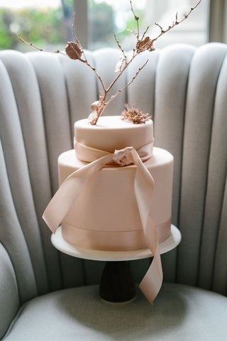 wedding-cake-on-tufted-settee-chair-channel-tufts-pink-cake-two-layer-rose-gold-branch-and-ribbon