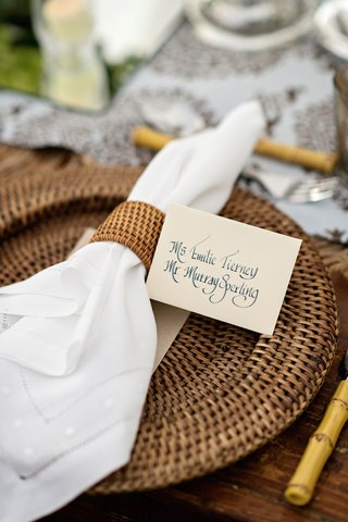 wedding-reception-place-setting-with-rattan-charger-and-napkin-ring-calligraphy-place-card
