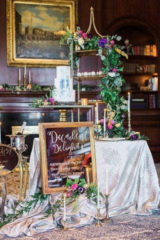 dessert-station-with-framed-mirror-sign-blue-wedding-cake-greenery