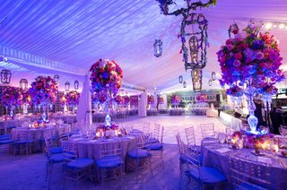 tented-wedding-reception-with-purple-and-pink-lighting-and-purple-and-pink-flowers