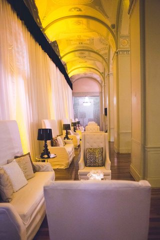white-wedding-lounge-furniture-with-metallic-throw-pillows-black-lamps-and-white-drapery