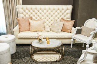 reception-seating-area-with-a-tufted-high-backed-couch-pink-pillows-and-white-chairs