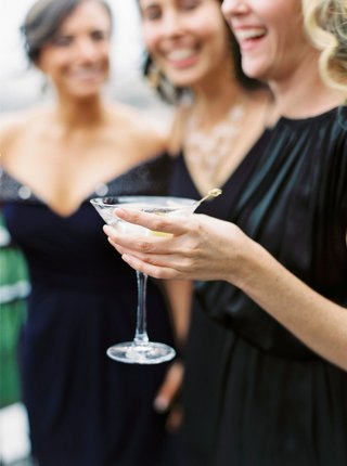 wedding-guest-in-black-dress-holding-martini-glass-with-olive-at-cocktail-hour-reception