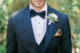 groom-suit-with-bow-tie-patterned-pocket-square-and-white-flower-boutonniere