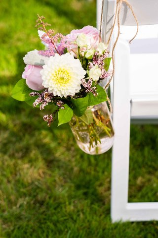 a-small-floral-arrangement-of-white-and-pink-flowers-and-foliage-glass-vase-hanging-white-chair