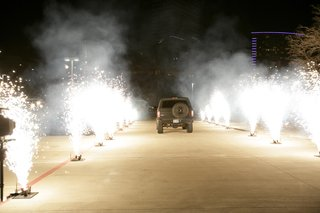 newlyweds-ride-off-in-truck-through-road-lined-with-fireworks