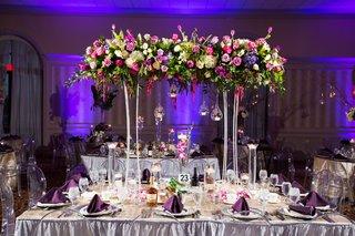 wedding-reception-silver-linens-purple-uplighting-tower-suspended-flower-arrangement-glass-orb