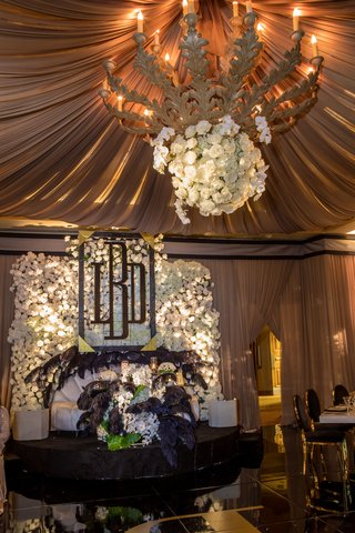 wedding-reception-sweetheart-table-flower-wall-monogram-chandelier-black-ostrich-feathers-white