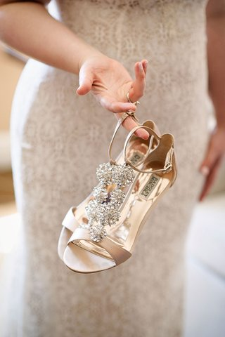 bride-holding-badgley-mischka-shoes-with-nude-and-crystal-details-ankle-strap-open-toe