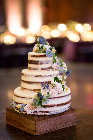 wedding-cake-naked-design-with-cascading-fresh-flowers-white-pink-purple-blue-on-wood-stand