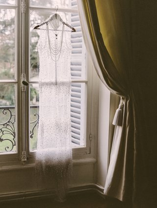 transparent-wedding-gown-with-pearls-by-melany-rowe-hangs-at-window-of-the-chateau-de-santeny