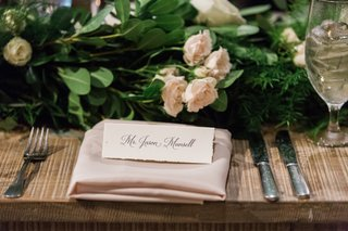 name-cards-on-blush-napkin-with-blush-flowers-and-green-leaves-and-silverwear