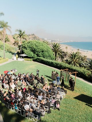 wedding-ceremony-on-grass-lawn-bel-air-bay-club-wood-arbor-beach-view-pacific-ocean