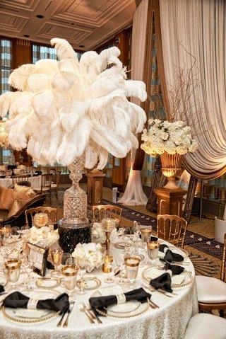 glam-vintage-inspired-wedding-reception-white-linen-black-bow-napkin-white-feather-tall-centerpiece