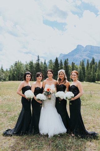 bride-in-watters-mermaid-wedding-dress-bridesmaids-in-black-gowns-with-sequin-bodices