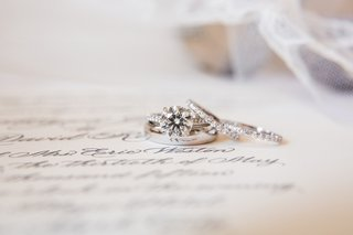 wedding-rings-or-bands-sitting-on-top-of-paper-with-cursive-calligraphy-delicate
