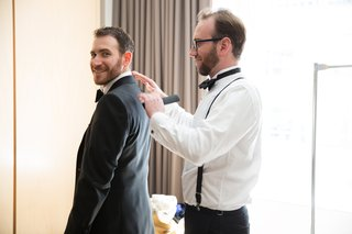a-groomsman-helps-the-groom-put-on-his-suit-jacket-before-the-ceremony