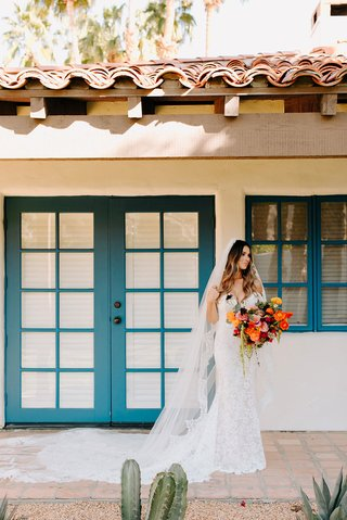 wedding photo of bride at la quinta resort and club lace wedding dress and veil colorful bouquet long hair