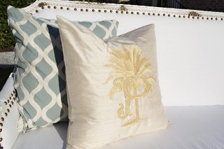 bride-and-grooms-wedding-crest-is-embroidered-in-gold-on-a-luxury-throw-pillow