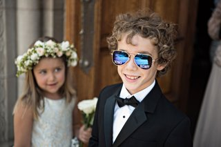 ring-bearer-in-tuxedo-and-bow-tie-with-mirror-aviator-sunglasses-that-say-ring-security-on-the-lense