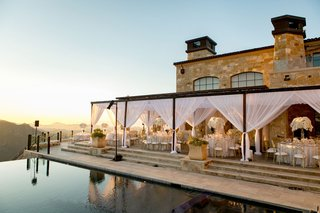 wedding reception set up by pool sunset view of santa monica mountains canyon white drapery gold